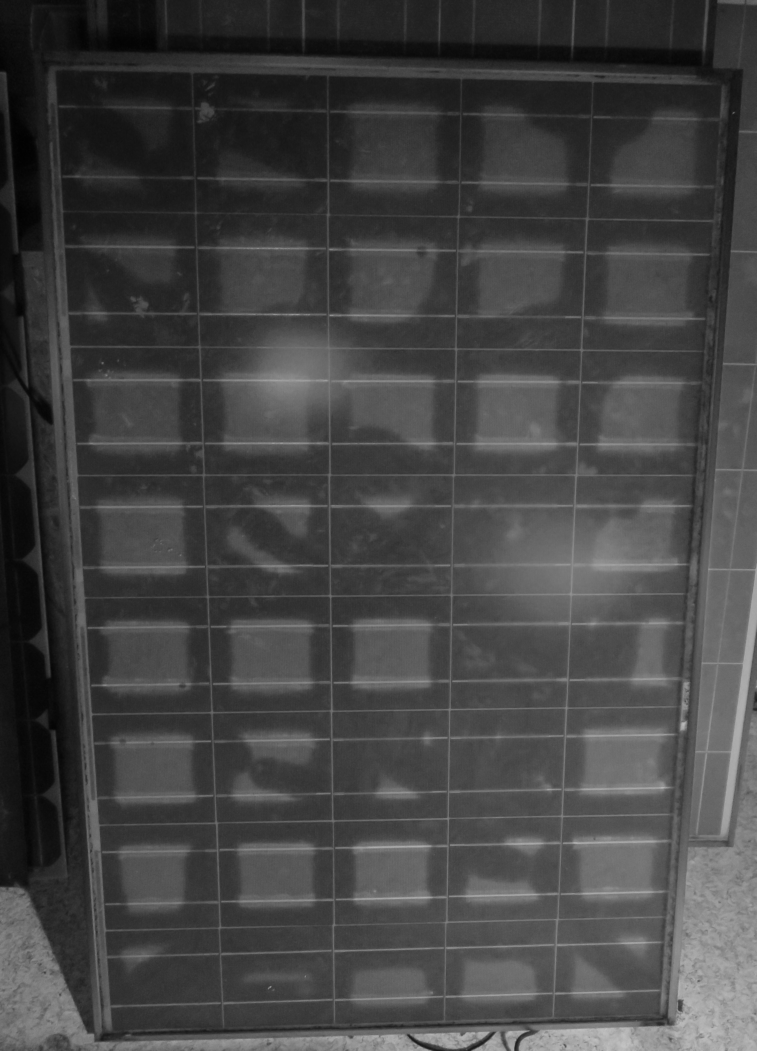 UV Floureszenz an Solarmodul mit mehreren Mikrorissen in den Solarzellen.